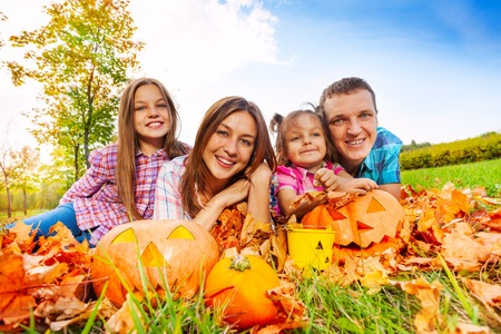 Happy family with two daughters lay in the autumn maple leaves smiling with Halloween pumpkins