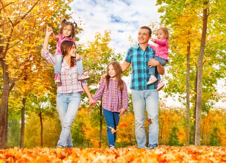 mom dad: Feliz joven papá de la mama de la familia y tres niñas caminan juntos en el parque otoño juntos tomados de la mano y llevar a los más pequeños Foto de archivo