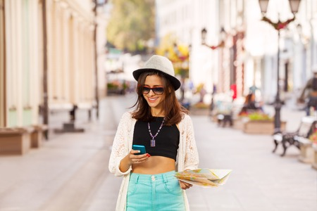 Woman with mobile phone and city map on the street during summer vacation time in Europe