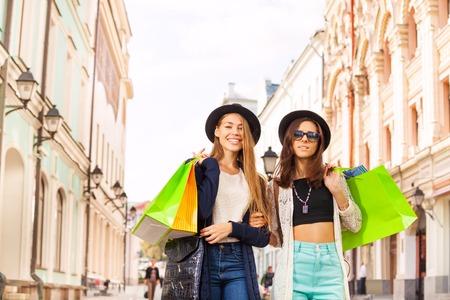 Gelukkige jonge vrouwen die met het winkelen zakken op de straat tijdens de tijd van de de zomerdag in Europa lopen
