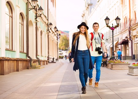 hold hands: Couple holding hands during walking on the beautiful street during summer day time Stock Photo