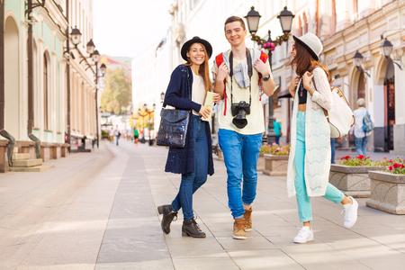 hilera: Tres amigos felices caminando en hacer turismo en la calle Europea durante el tiempo de día de verano en Moscú Foto de archivo