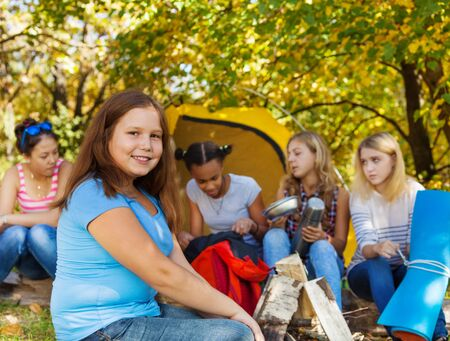 girl scout: Cute beautiful girl sitting near yellow tent with her friends during sunny autumn day at campsite Stock Photo