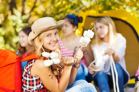 youth group: Positive girl wearing hat holds sticks with marshmallow sitting near yellow tent with her friends during sunny autumn day on the campsite