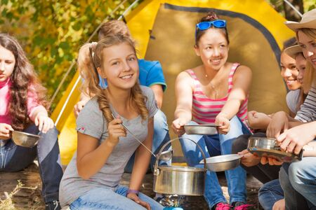 black teens: Smiling girl cooks soup in the pot near yellow tent with friends sitting during autumn day in the forest at the camping site