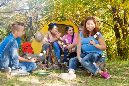 girl scout: Teen friends sit on campsite with marshmallow sticks near fireplace with yellow tent during autumn day in the forest Stock Photo