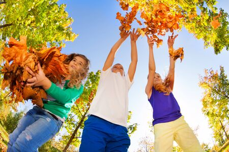 children hands: Fish-eye view of friends playing with thrown leaves in the forest together during beautiful autumn sunny day Stock Photo