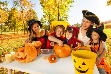 Family in costumes craft Jack-O'-Lantern from pumpkin sitting at the table during Halloween outside at beautiful sunny autumn day Banco de Imagens