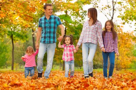 mom dad: Feliz papá de la mama de la familia y las niñas caminan tomados de la mano feliz en el octubre hojas de arce parque