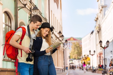 Young man and girl as tourists with map sightseeing on the European street during summer day time Banco de Imagens