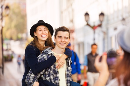 laughing: Boy holding laughing woman and girl shooting them with professional camera on the European street during summer day time Stock Photo