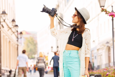 Girl wearing sunglasses shooting with camera touristic attractions on the street during summer day time