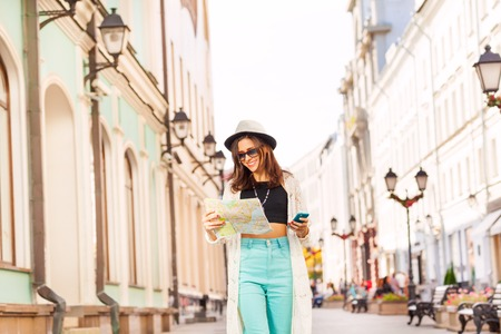 beautiful girl: Girl holds mobile phone and city map on the street during summer vacation time in Europe Stock Photo