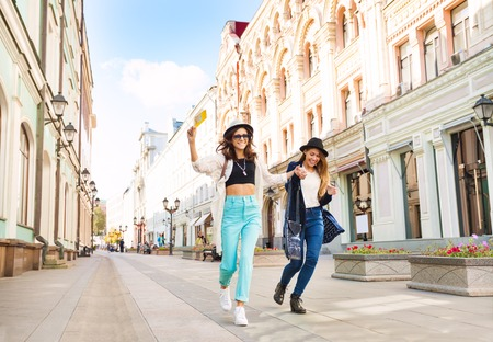 Two happily jumping girls while walking holding hands on the beautiful street in Moscow