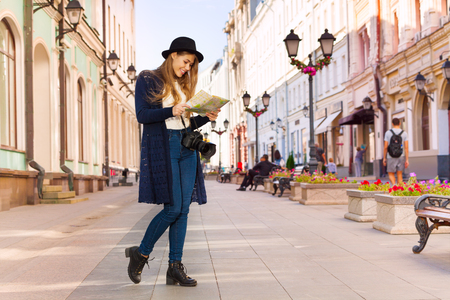Smiling girl in retro outfit holding city map on the European street during sightseeing at summer day time Stock Photo - 49177846