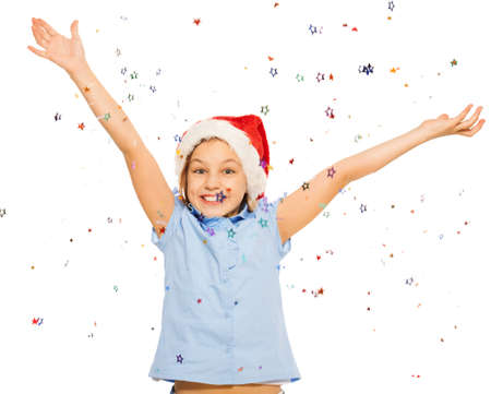 lifted hands: Happy beautiful girl in Santa cap throw up confetti with lifted hands and cute smile