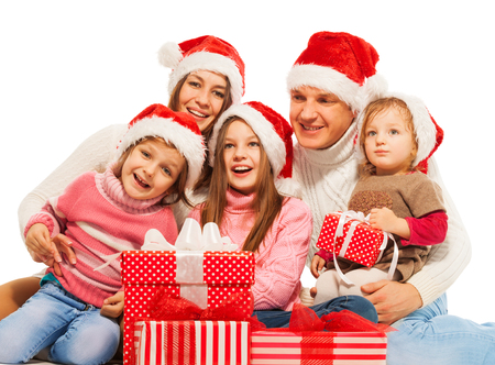 family isolated: Big happy family with Christmas presents together sitting and wearing Santa hat isolated on white