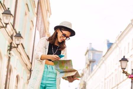 europe closeup: Close-up of girl with mobile phone and city map on the street during summer vacation time in Europe