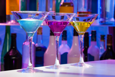 cocktail glasses: Three cocktail glasses standing on the bar table with different colors drinks Stock Photo