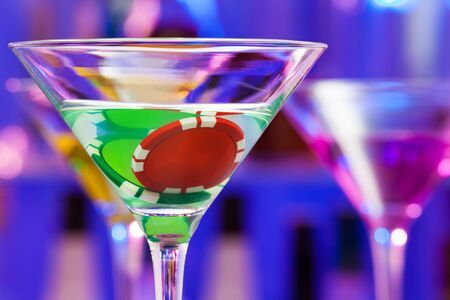 token: Close-up of martini glass with casino chip token in the drink in the bar background Stock Photo