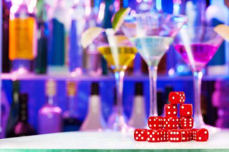 limón: pila rojo de los dados sobre la mesa de bar con copas de c�ctel en el fondo