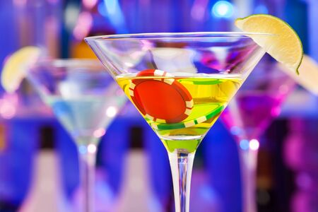 casino tokens: Casino chip in the martini glass drink with bar bottles on background Stock Photo