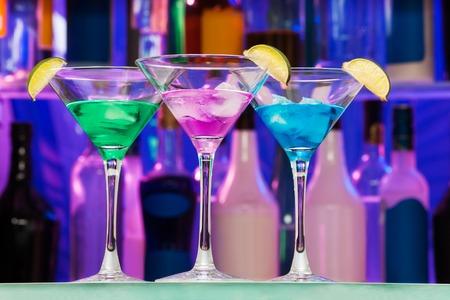 coctel de frutas: Diversas bebidas alcohol cóctel con cal en los vasos y botellas en el estante de la barra