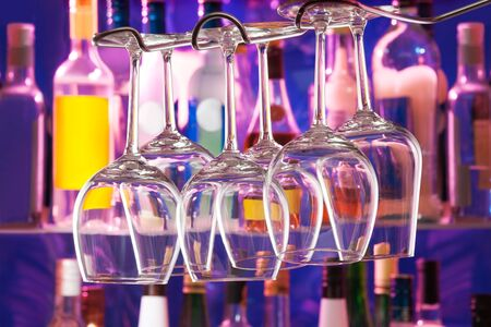 winy: Night bar with bottles and color lit background and wine glasses hang upside down Stock Photo