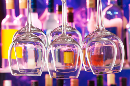winy: Many wine glasses hanging in the bar upside down with color lit bottles on background Stock Photo