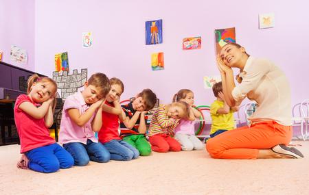 Groep van kinderen spelen slaap spel met leraar hand in hand en laten zien slapen gebaar