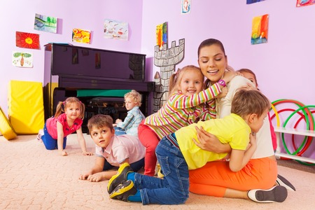 Group of kids in kindergarten hugging teacher playing on the floor