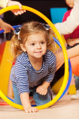 Portrait of little girl go though hoop plying active game in kindergarten