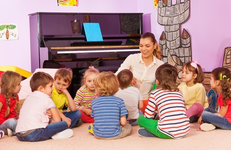 아이들의 그룹은 선생님과 함께 앉아서 이야기를 듣고 그녀는 유치원 방에서 이야기 스톡 콘텐츠