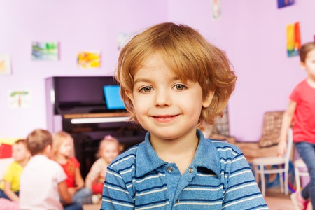 mignonne petite fille: Closeup portrait of nice little boy smiling with his friends sit in the room on background