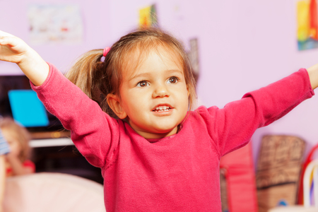 children hands: Happy little girl lifting hands up and smile, close portrait in the room inside Stock Photo