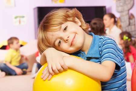 Happy smiling boy hug yellow ball quiet and smiling with other boys and girls on background in kindergarten group