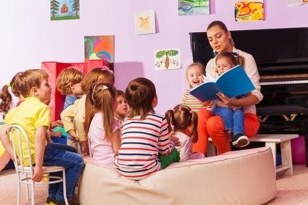 ni�os leyendo: Gran grupo de ni�os sentarse y escuchar a la maestra lee un libro y contar historias Foto de archivo