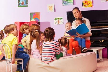 Large group of kids sit and listen to teacher reading a book and telling stories Stock Photo