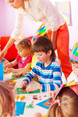 gluing: Little boy portrait on handmade kindergarten class gluing paper to cardboard and teacher helps other kids on background Stock Photo
