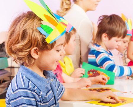 educator: Boy in handmade headwear gluing paper to cardboard in class with nurse and kids on background Stock Photo