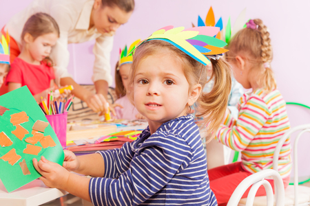 mates: Little girl glue paper to cardboard in crafting kindergarten class with mates and teacher helping on background
