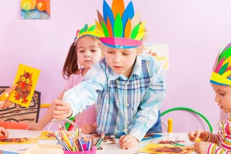 indian headdress: Boy reaching pencils wearing Indian headdress  during craft lessons in kindergarten Stock Photo