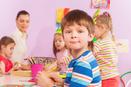 Portrait of a nice smiling boy in kindergarten class look at camera with mates and teacher on background