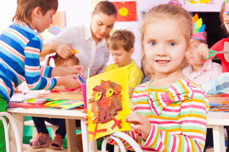 Little girl with craft made of of paper and cardboard and group of kids and teacher on the back occupied