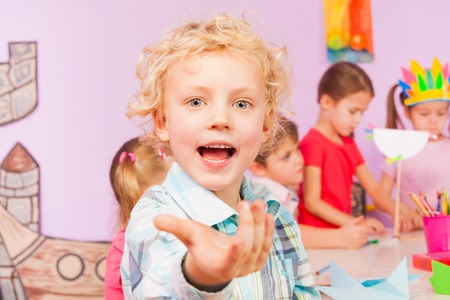 Little blond boy invite and call viewer to join his preschool development class with other kids Stock Photo