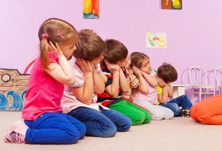 Group of kids in kindergarten sitting in a row and pretending to be asleep
