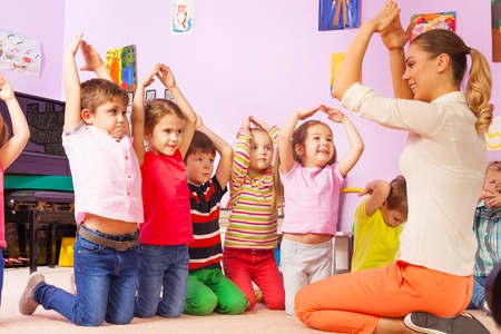Group of kids repeat gesture after the teacher in kindergarten class making house with hands above head