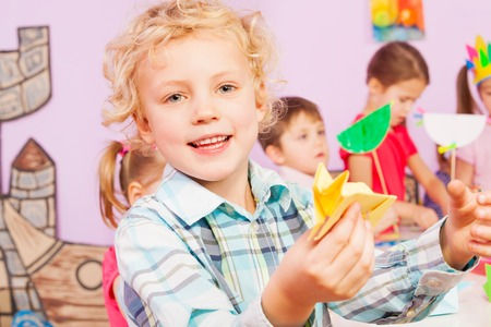 preschoolers: Handsome little boy with origami in the classroom with other preschoolers