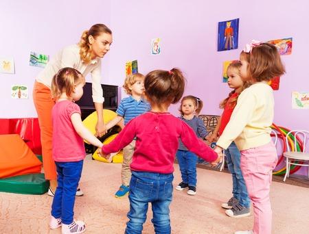 educators: Maestro y grupo de niños en la guardería con estribillo en kindergarten lección