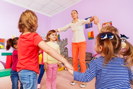 lift hands: Group of children playing roundelay with teacher in kindergarten class make circle around girl and lift hands